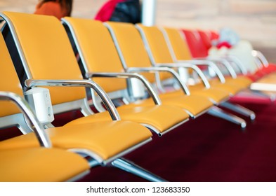 Row of orange seats with electric socket in airport