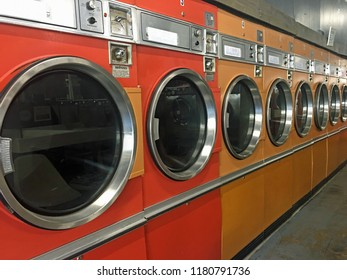 Row of orange and yellow dryers in laundromat