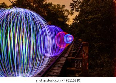 A row of Orbs on a train track - Abstract Light Painting at night - Light Art Photography