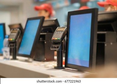 Row of order desks with computer screen and card payment terminal in fast food restaurant