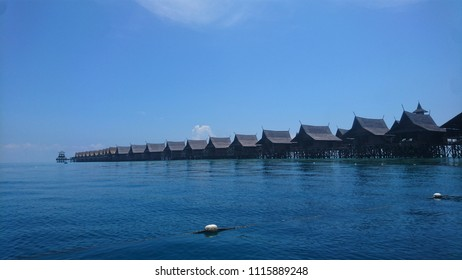 A row of over water bungalows under the clear blue sky