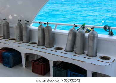 Row of oxigen tanks for scuba diving on the boat on the blue sea background.