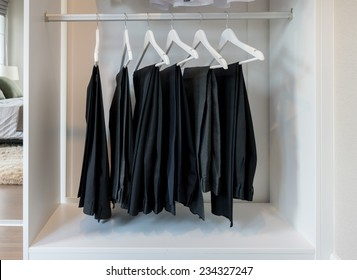 row of pants hanging on coat hanger in white wardrobe