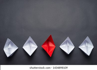 Row of paper ships on black background. Business concept of creative innovation and leadership. Flat lay red origami boat in group of white boats. Corporate strategy and successful solution.