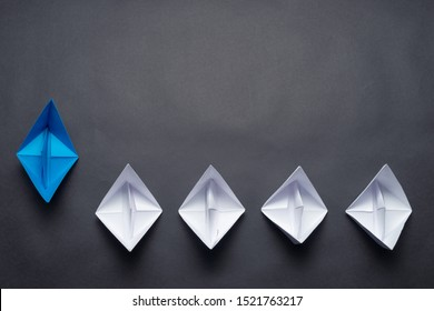 Row of paper ships on black background. Business concept of creative innovation and leadership. Flat lay blue origami leader boat ahead others boats. Social marketing layout with copy space.