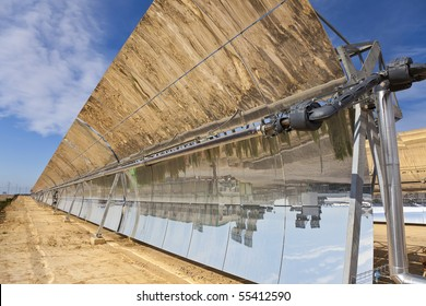A row of parabolic trough solar mirror panels harnessing the sun's rays to provide renewable alternative green energy