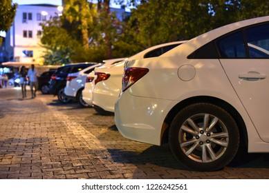 row of parked cars on night street