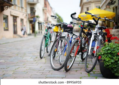 Row of parked colorful bikes on a street