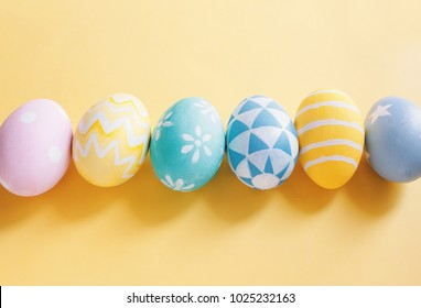 Row of pastel and colorful easter eggs with copy space on yellow background