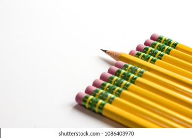 Row of pencil tops enter on an angle from bottom right with erasers flush and pointing toward center. Seventh pencil in stands out with sharpened lead tip jutting out further than adjacent erasers.