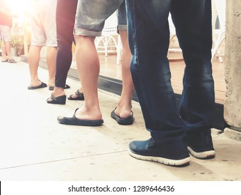 Row of People in queue for waiting something. Back of man and woman orderly in line. Close up legs of people