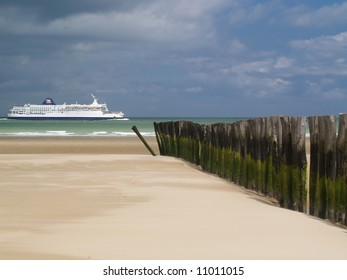 Row of pilings on beach pointing to ferry at sea, Calais, France