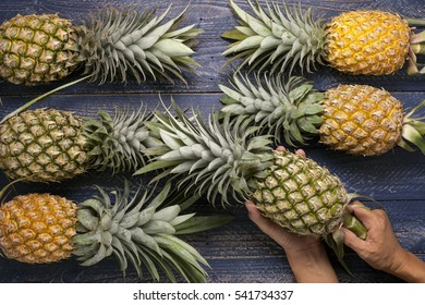 Row of pineapple fruits on wooden table background