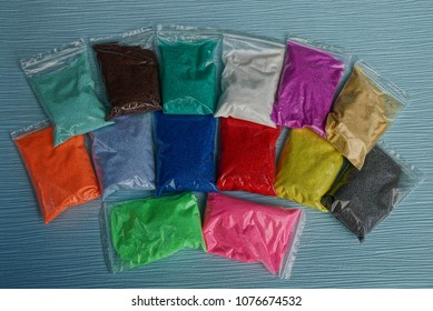 A row of plastic bags with colored sand on a blue table
