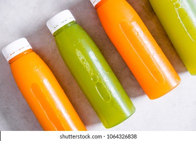 Row of plastic bottles of cold-pressed unprocessed fruit and vegetable juices, from above, light gray table. Body cleance, fast concept. Minimalism food photography. Closeup