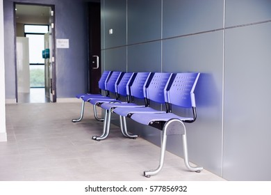 Row of plastic chairs in walk way. Purple plastic chair.