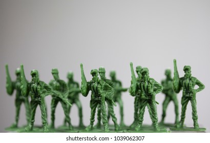 Row of plastic little green army men, close up.
