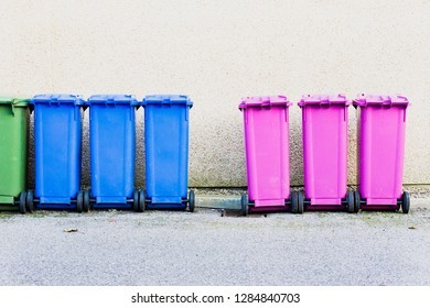 A row of plastic waste bins for collection in front of a stone wall