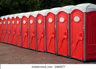 A row of portable red toilets at an outdoor event