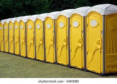 A row of portable yellow toilets at an outdoor event