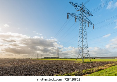 Row of power pylons at the edge of a plowed field. It  is a sunny day in the beginning of the Dutch fall season.