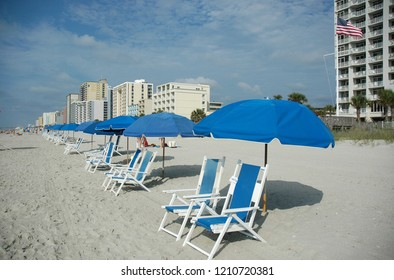 A row of pretty blue beach chairs and umbrellas at the seashore.