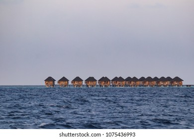 Row of private luxury hotel bungalows built on stilts out over the ocean