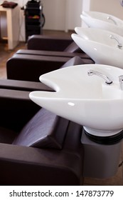 Row of professional curved washbasins with indents for a persons neck in a hair salon with empty comfortable chairs in front of them