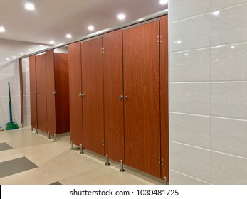Row of public toilet, wooden door in public restroom