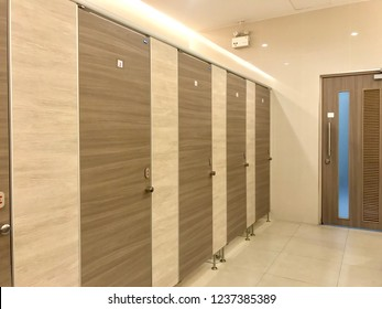 Row of public toilet, wooden partition in public restroom
