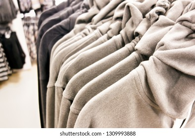 A row of pullovers hanging in store. Close-up.