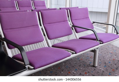 row of purple chairs in the airport