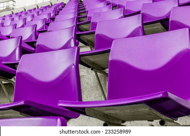 row of purple plastic chairs that disappear into the distance