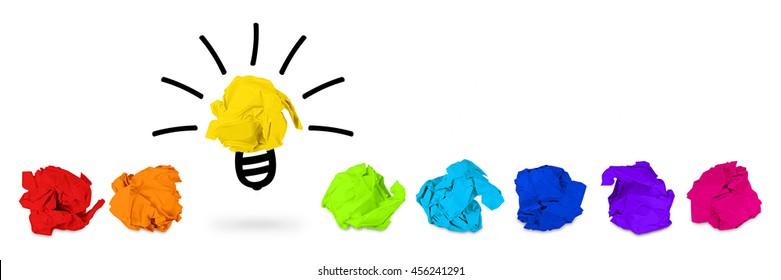 row of rainbow colored paper balls with idea light bulb symbol