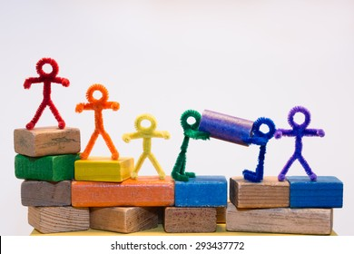 A row of rainbow pipe-cleaner people across children's building blocks with two helping each other to move a block. Wonderful photo for multicultural, international ideas and concepts.