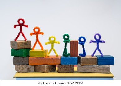 A row of rainbow pipe-cleaner people across children's building blocks with two sharing or helping each other with a block. Wonderful photo for multicultural, international ideas and concepts.