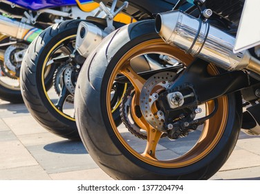 row of rear wheels of sports bikes in competition close up