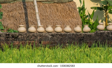 A row of recently thrown pots dries in the sun on a brick wall by a rice field in front of a haystack.