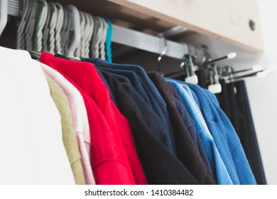 Row of red and blue t-shirts hanging on the hangers in gradient pattern and black slack hanging in the background inside dressing room