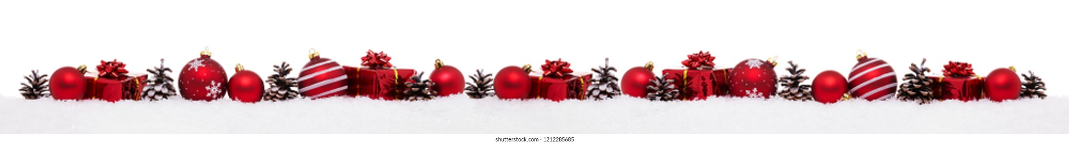 Row of red christmas baubles with xmas present gift boxes isolated on snow