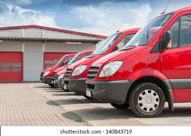 Row of red delivery and service van, trucks and cars in front of a factory and warehouse distribution plant