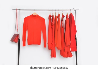 Row of red different clothes ,sweater, long shirt ,sundress on a hanger