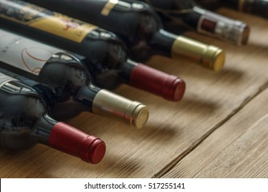 Row of red dry wine bottles  on wooden background. Low depth of field.