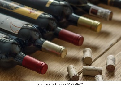 Row of red dry wine bottles and wine corks  on wooden background. Low depth of field.