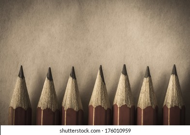 A row of red pencils with tips facing upwards against parchment textured paper which provides copy space above. Processed in a retro or vintage style.