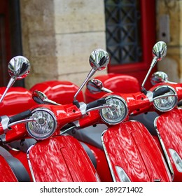 Row of red retro scooters parked on a Parisian street
