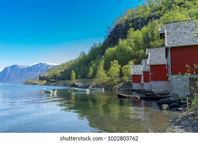 A row of red small house with small boats at Flam, Norway