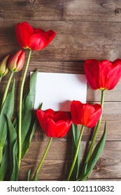 Row of red tulips on wooden background with space for message. Women's or Mother's Day background. Spring flowers