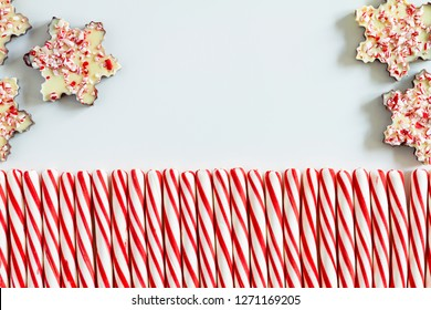 Row of red and white candy cane sticks with chocolate peppermint bark snowflakes and copy space