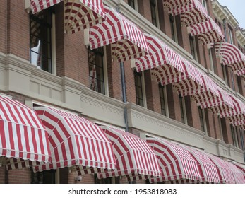 row of red and white stripe awnings on houses in Amsterdam